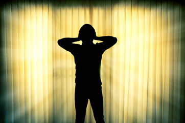 Silhouette of frustrated man with light ray effect background