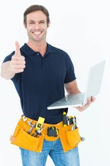 Worker holding laptop while gesturing thumbs up