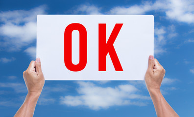 Two hands holding brown cardboard with ok on blue sky background