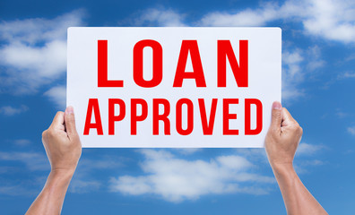 Two hands holding brown cardboard with loan approved on blue sky