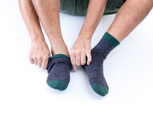 Man putting socks on white background