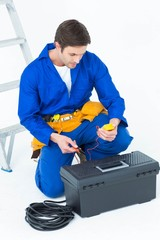 Electrician using multimeter over white background