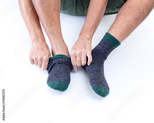Man putting socks on white background - 76967279