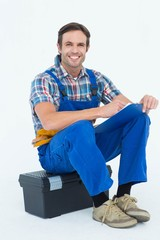 Plumber writing notes while sitting on tool box