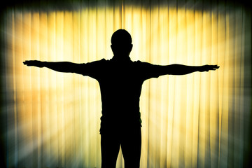 Silhouette man showing his hands like a cross with light ray eff