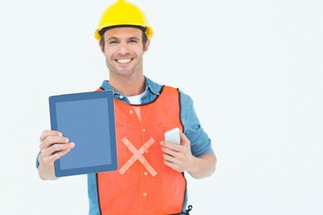 Carpenter holding digital tablet and mobile phone