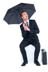Smiling businessman under umbrella sitting on cube