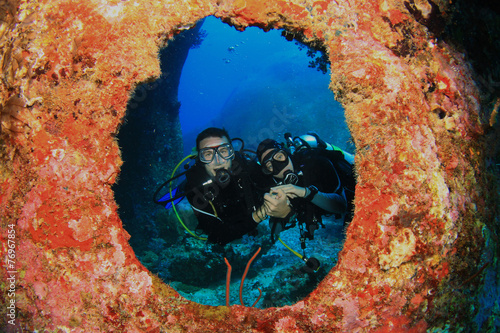 Aluminium Duiken Scuba diving couple framed by coral