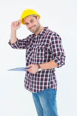 Happy repairman wearing hard hat while holding clipboard
