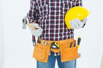 Handyman holding hard hat and hammer