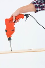 Male carpenter drilling hole in wood