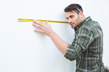 Carpenter measuging white wall with measure tape