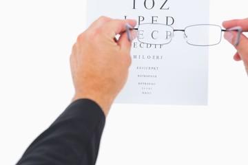 Man holding eyeglasses over paper