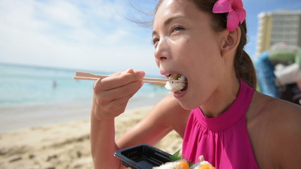 Woman eating sushi take out on beach