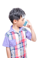 Sick Asian boy using inhaler for asthma on white background