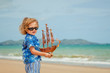 little boy standing on the beach at the day time