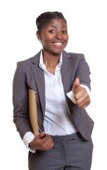 Lachende Geschäftsfrau aus Afrika mit Akte zeigt den Daumen