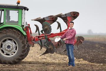 Happy farmer beside plough