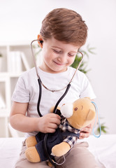Adorable child with stethoscope of doctor examining teddy bear