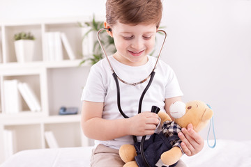 Child with teddy bear playing a doctor