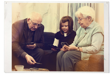 Grandparents playing cards with grandchild