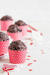 Chocolate muffin with red hearts on white background