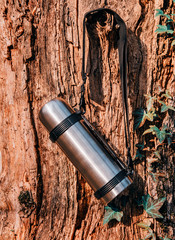 Thermos hanging on a tree