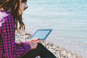 Woman sitting with digital tablet on beach