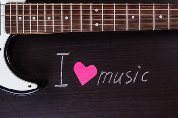 """Electric guitar with text """"I love music"""" on dark background"""