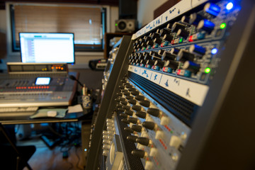 several mixing consoles in a recording studio