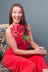 girl sitting on chair with  flower and laughs
