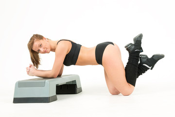 young woman does exercises on step