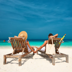 Couple in white relax on a beach at Maldives