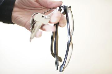 Person hält Brille und Schlüsselbund