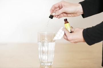Schmerzmitteltropfen in Wasserglas geben