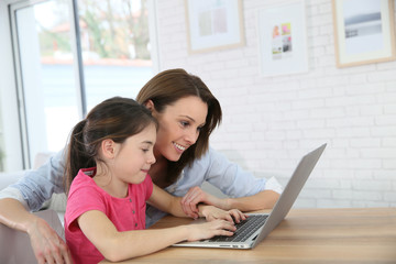 Mother and daughter playing on laptop computer