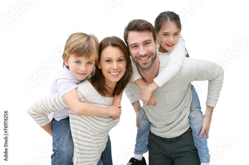Young parents giving piggyback ride to kids - 76976256