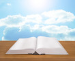 Open book on wooden plank bright sky background