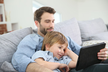 Father with little boy using digital tablet at home