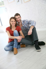 Trendy couple sitting on house floor