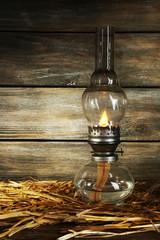 Kerosene lamp with hay on rustic wooden planks background