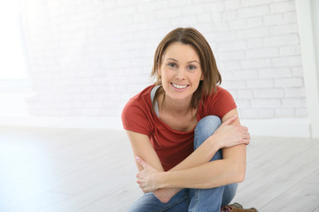 Portrait of young trendy woman sitting on floor