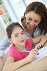 School girl with mother learning to write