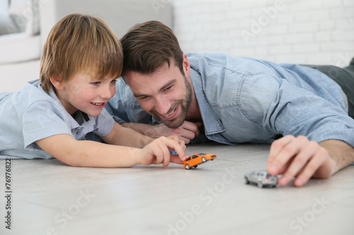 Daddy with little boy playing with toy cars - 76976822