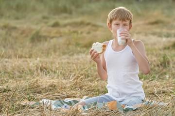 Teenage farmer boy tasting fresh milk and bread