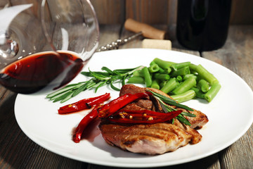 Glass of wine and steak with vegetables