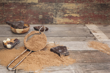 Chocolate pieces and cocoa powder on wooden background