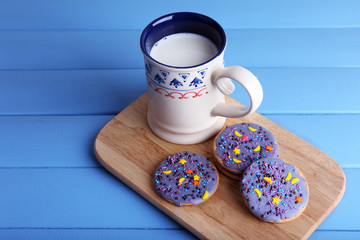 Three glazed cookies with cup of milk