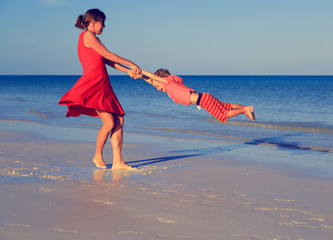 mother and son playing on summer beach