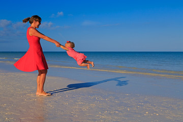 mother and daughter playing on summer beach